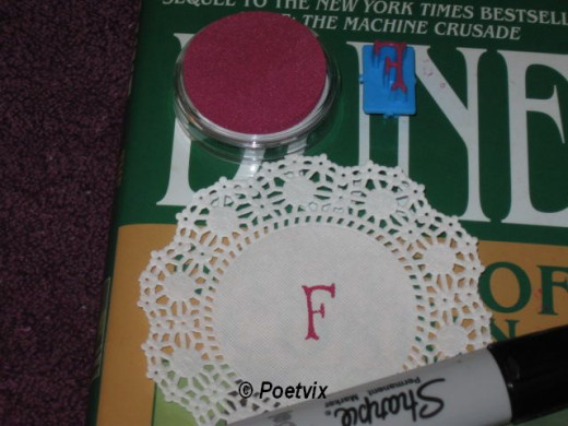 Stamp the small doilies with the letters you pick to spell out the word or words of your choice. You could hand write this step or glue down printed or cut out words.