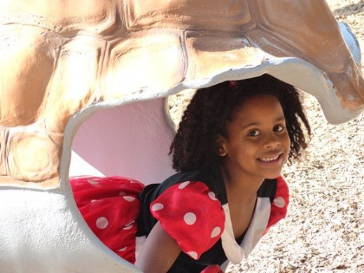 My beautiful granddaughter poses in the shell of a turtle at the zoo.
