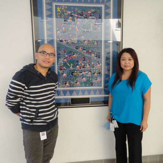 Eldrick Chang and Say Xiong in front of the story quilt at the Fresno Adult Community Education center.