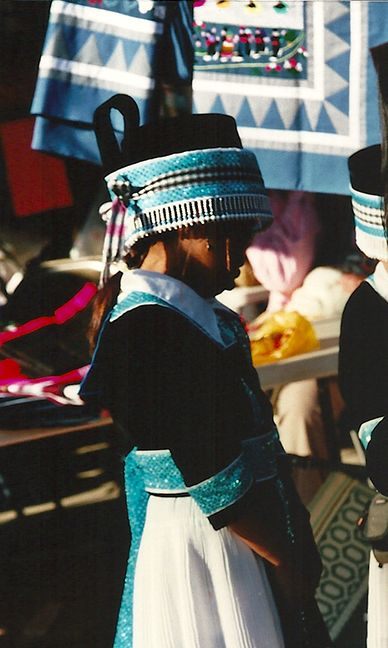 Another photo from the Hmong New Year celebration. Behind the young girl are more story quilts for sale with the traditional blue and grey border.