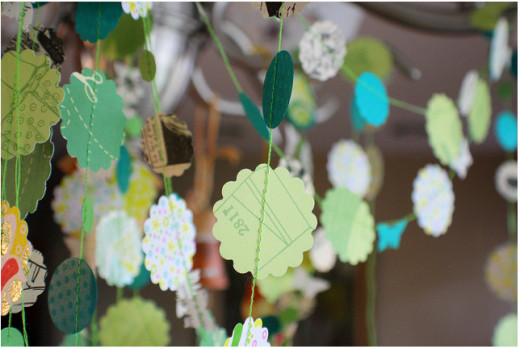 You can make pretty garlands like this by simply using a punch to cut out shapes in thin card/paper (or cut them out individually) and sewing straight through them with a sewing machine, leaving a gap between each.