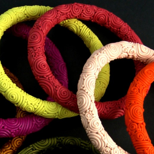 The clay core of the bangles is baked first, and then the clay swirls and spirals are added after.