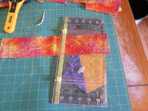 Add 3 inch strips to each side, and cut away access fabric. Cut strips longer in case you have trim them off on an outward angle.