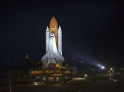 Bathed in xenon lights, space shuttle Endeavour moves along the crawlerway f