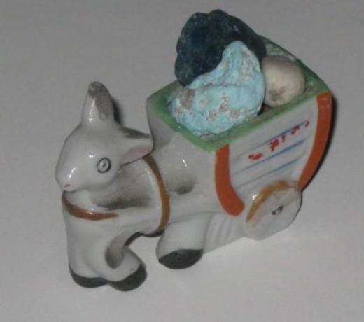 Donkey figurine pulling a cart full of rocks. He's one tired donkey.