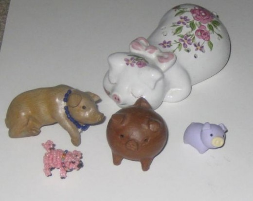 This collection of pigs includes a brown pig that hangs from the spine of a book, a small pink beaded pig, a round fat pig, an Avon sachet pig, and a tiny purple eraser pig.