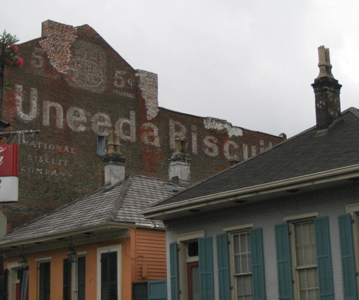 Uneeda Biscuit ghost sign with lovely French Quarter buildings in the foreground.