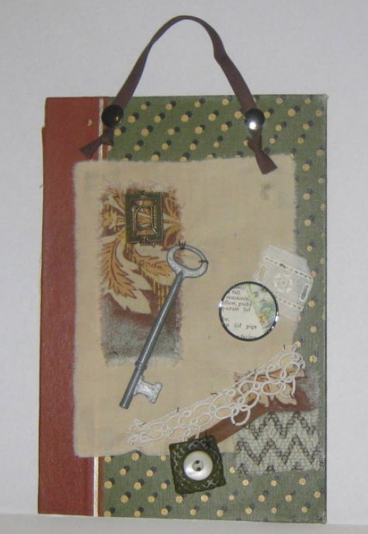 Mixed media collage using a book cover for the base and found objects like fabric, lace, skeleton key, and polymer clay/vintage button tile.