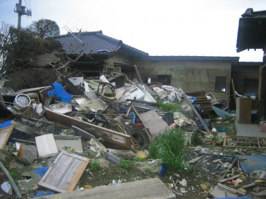 Damaged homes with piles of debris.