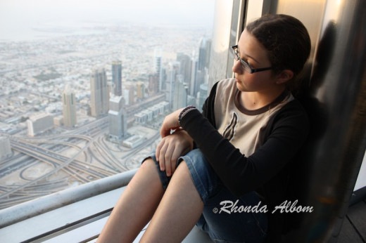 My daughter sits in the window well on the outdoor deck of the observation level of the world's tallest building.