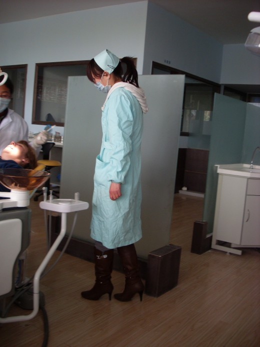 The nurse with a theatre gown covering her short nurse's uniform and boots.