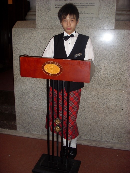 Bell boy dressed in a kilt at the 1846 Astor House Hotel in Shanghai.
