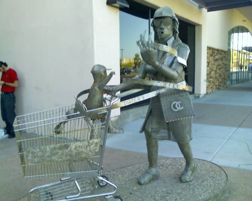Sculpture of Woman entangled in cash register receipt an pushing her child in a grocery cart