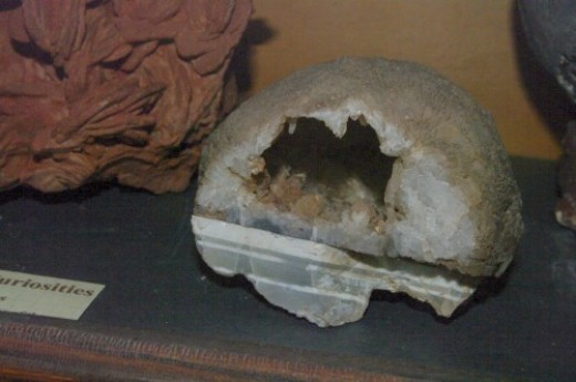 Geode, sliced in half so you can see the interior is hollow and lined with crystals.