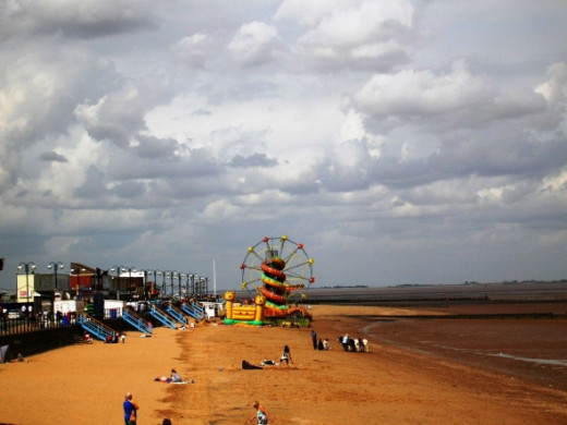 Back to the more sociable end of the beach, looking along toward the childrens' amusements. There is a snake helter skelter, and a  dragon ride, big wheel, bouncy castle and swing carousel.