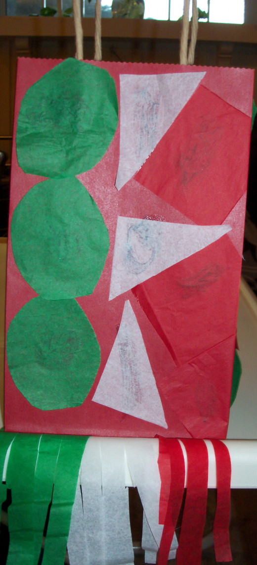Young children can paste precut shapes or simply cut or tear tissue paper to paste onto their bags. (Young children LOVE to cut with scissors!)