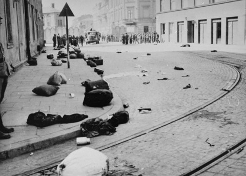 Major street in Krakow strewn with the bundles of deported Jews after the liquidation of the ghetto. [n]
