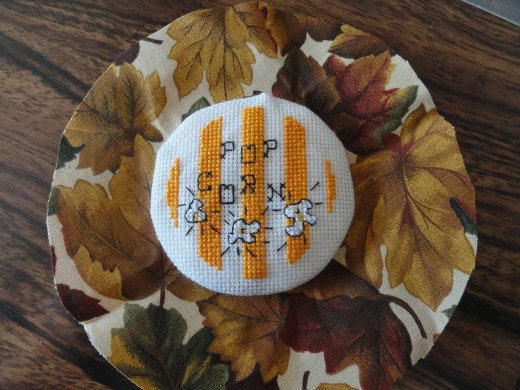 Glue cross stitch design to the fabric to make jar lid.