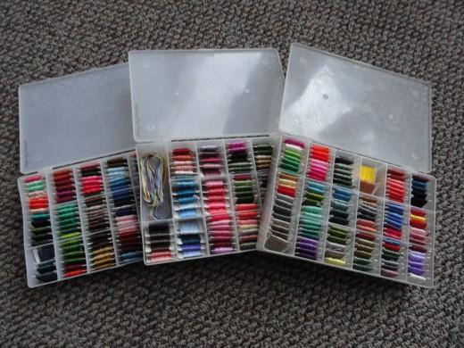 Three organizer storage boxes of cross stitch floss.