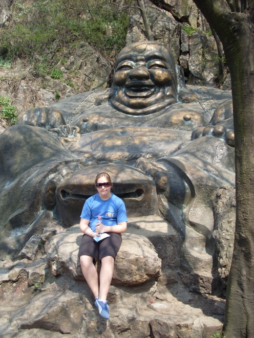 The youngest sitting next to a big Buddha on the top of Purple Mountain.