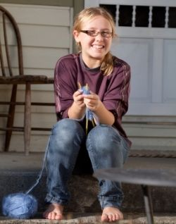 girl knitting on front step