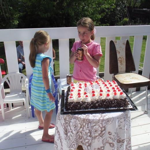 Children eyeing up the cake at a backyard wedding.