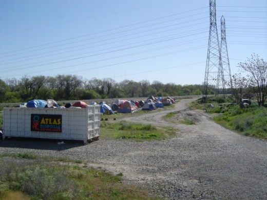 A refuse bin is the only amenity in Sacramento's tent city.
