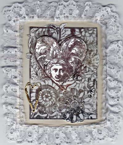 Silver and white vintage Valentine with frilly lace around the edge.