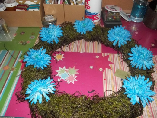 Larger flowers should be placed first equally around the wreath form