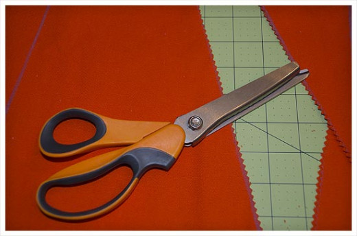Use pinking shears to cut the triangle pennants. Cutting with pinking shears will help keep the material from fraying.