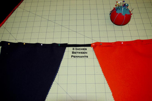 I spaced my pennants three inches apart. The pennants were nine inches across. 9+3 = 12 inches.I used a pattern of black & orange alternating colors.