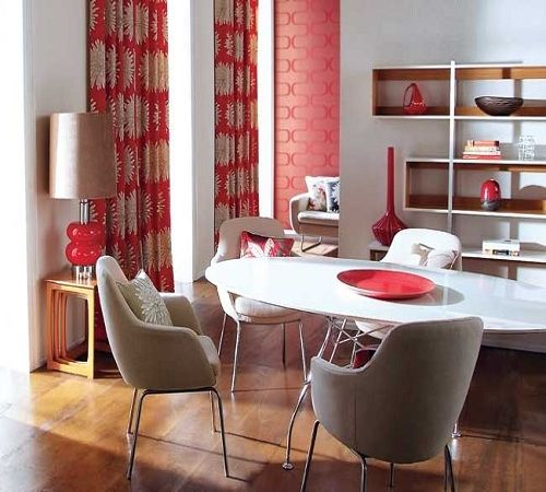 Notice how effectively the inclusion of the bold and bright orange-red draperies, accent wallcovering and other red accessories play off the rest of the neutral room?  By keeping the color scheme simple, the pop of color is not overpowering, but serv