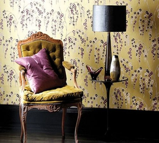 An archive-inspired Art Deco wallcovering from Harlequin, pattern 'Iola'. Notice the ebony base trim and flooring, as well as the modern black side chair and sleek table lamp with drum shade.  Go ahead and mix in a traditional button-tufted, velvet-u