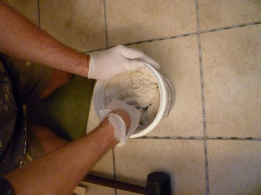 """After a couple of minutes of using his 3"""" broad knife to bring up the sand from the bottom, the grout is almost completely mixed."""