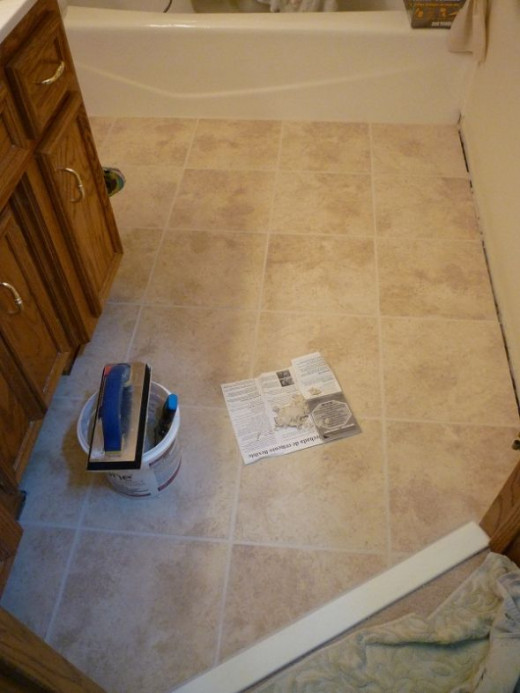 All done grouting!  It took about 45 minutes to grout the hall bath floor.  Notice the unfilled area along the wall. That will be filled with silicone caulk after the grout has dried and before the base trim is re-installed. The blob of grout on the