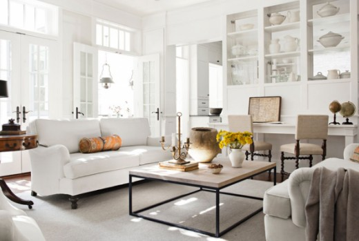 Modern white/neutral colored livingroom uses large pieces to display, shelving, high ceilings & large windows make this room look larger than usual.