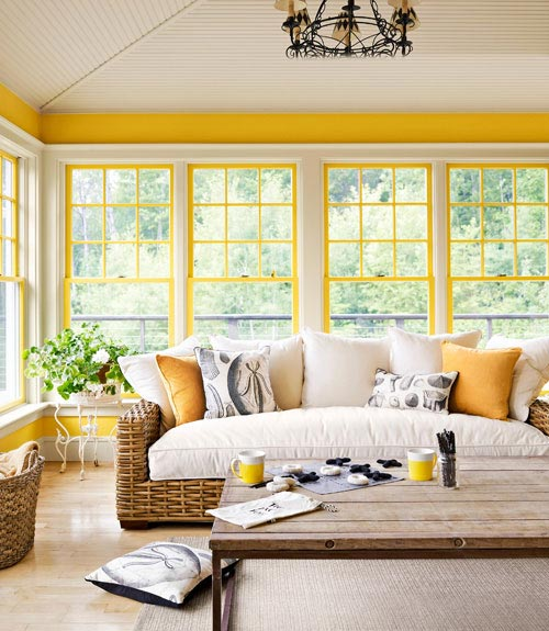 Sunrooms & porches look bright with yellow accents.  Oversized rattan sofa & baskets add a sense of down home to the room.