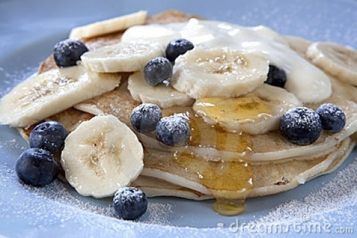 Blueberry pancakes with bananas and honey syrup.