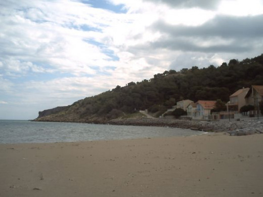 Lovely sandy beach at the bottom of a pine forest covered hillside