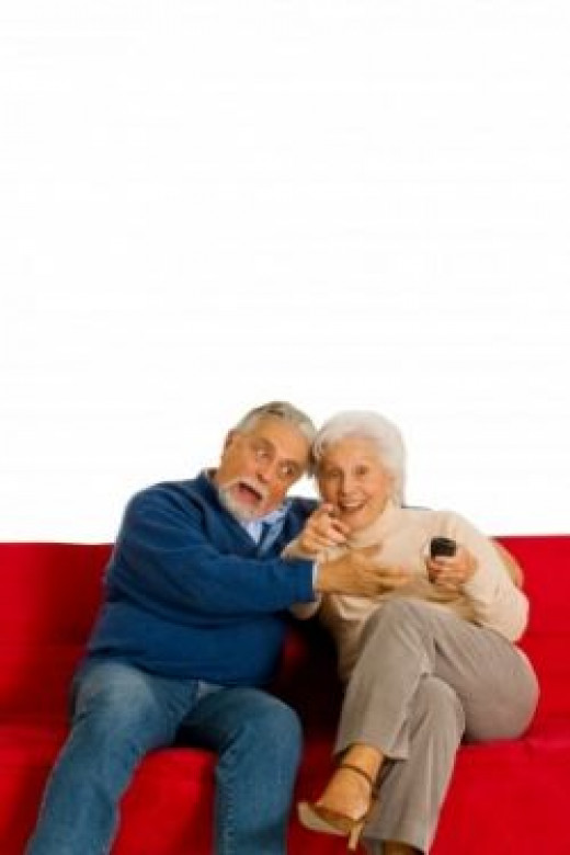 Elderly couple with remote for TV