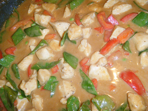 Now the peanut sauce has been added to the chicken and vegetables. Continue to cook.