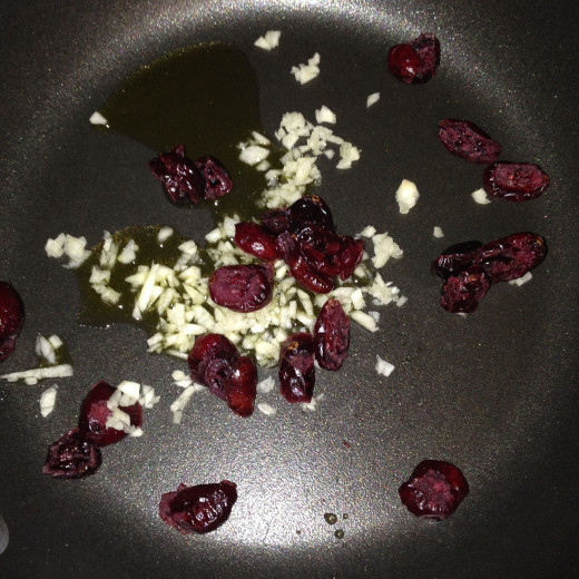 Garlic and dried cranberries in olive oil in pan on low heat