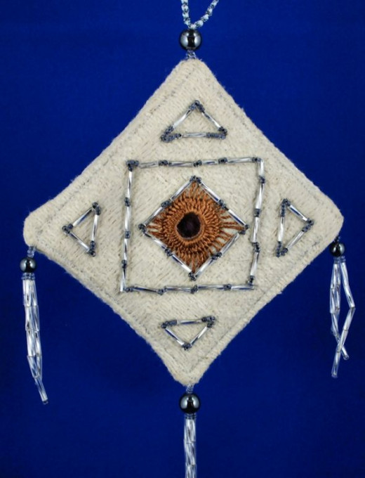 Bugle and seed beads surround the mirrow in this decorations.  The round beads at the corners are black hematite.