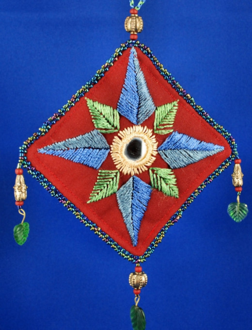 The stylized leaves surrounding the mirror in this decoration was done using rayon embroidery thread.  There's a seed bead edging, with metal beads and plastic leaf beads instead of a fringe.