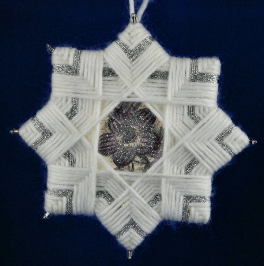 White yarn and silver metallic crochet thread frame a flower cut from scrapbook paper and accented with silver glitter glue.