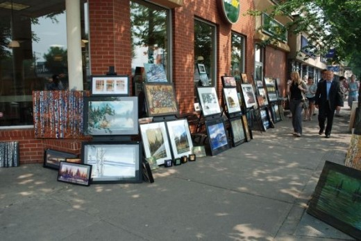Pedestrians enjoying the work of several artists along Whyte Ave.