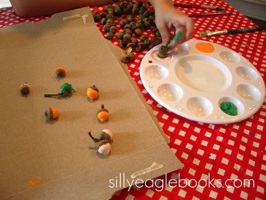Dipping acorns in paint is one way to decorate them.