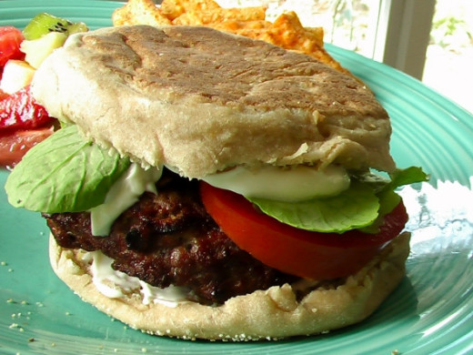 Burger on an English muffin with lettuce, tomato and plenty of mayonnaise.