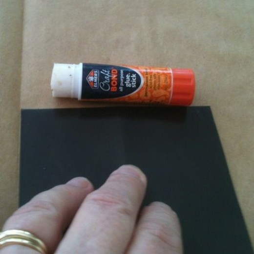 Use a glue stick and cover the front of the ad and place it face down on the wrong side of the paper you are using.