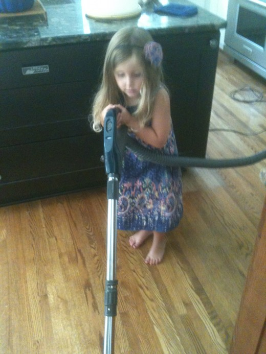 A teachable moment. My grandchild learns to use the vacuum cleaner.